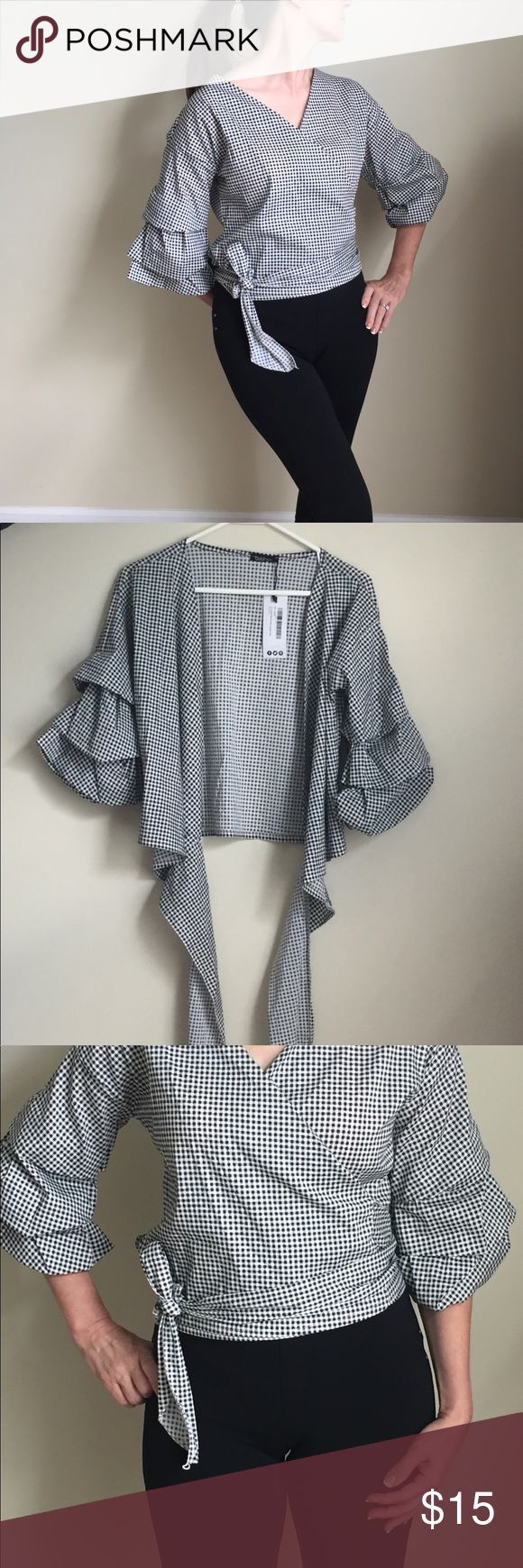 """Ruffle statement sleeve blouse Classy blouse. Never worn. Original tags. Black and white gingham/checkered. 70% Cotton, 27% nylon, 3% elastane. Model is 5'4"""", 125 lbs. Tops Blouses"""