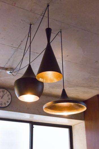 ダイニングテーブルを照らすのは、トム・ディクソンの照明。真鍮の素材感と異なる形状が面白い。