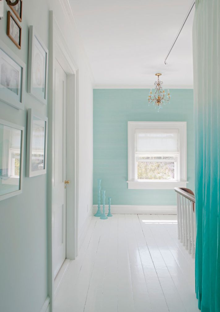 Pale turquoise walls, white floors, gold chandelier, and ombre curtain.