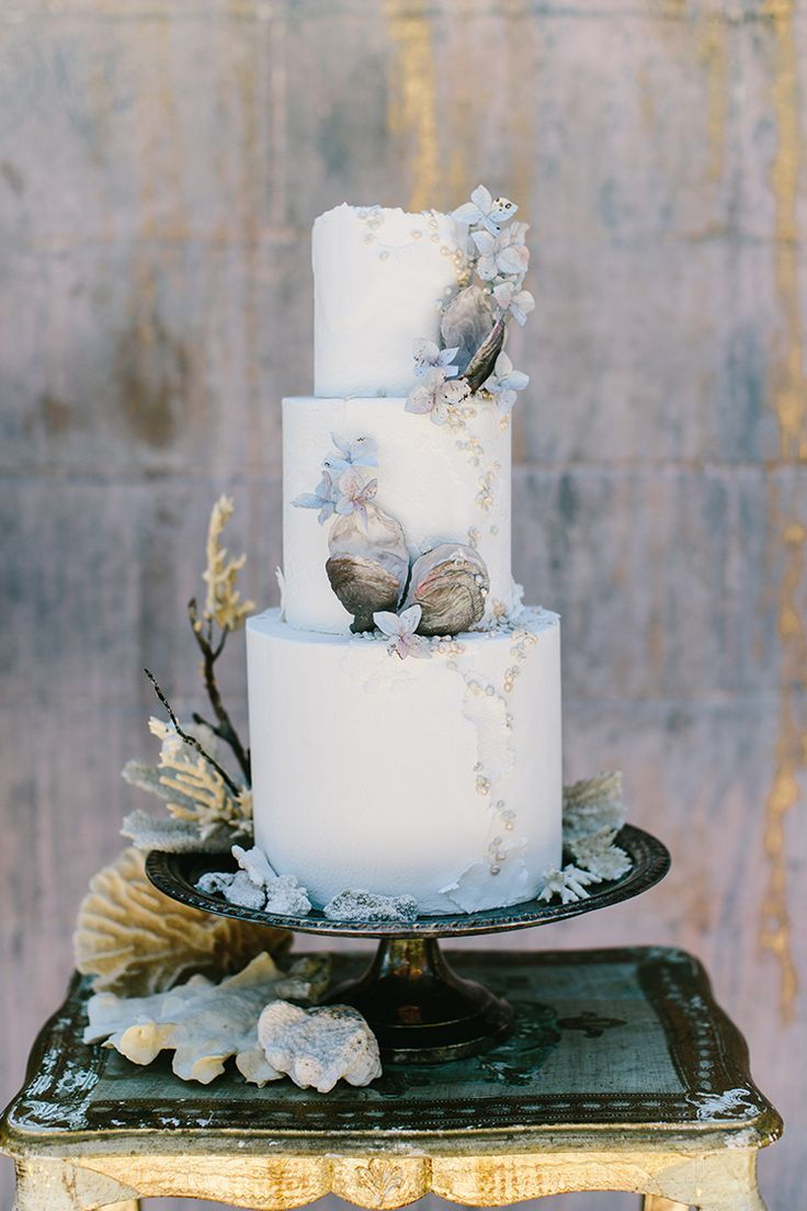 Wedding Cakes Beach Wedding Cake | This three tier fondant wedding cake is absolutely perfect for a classy beach wedding reception. It's soft blue hues and tasteful placement of sea shells add just the right amount of detail to this asymmetrical cake