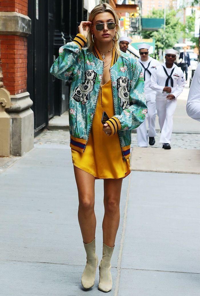 Tenue créative, robe courte en soi jaune, blouson boyfriend vert à motifs blanc et noir, manches et côtés noir et jaune, bottes beiges, lunettes de soleil, boucles d'oreilles