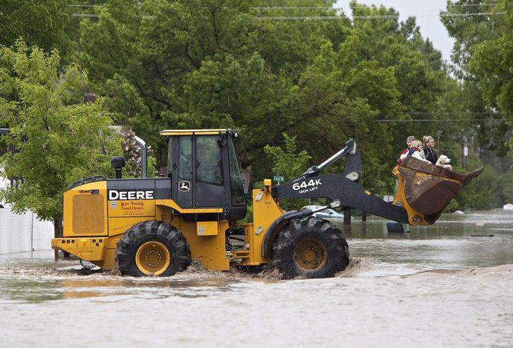 A front end loader carries residents after they were rescued from the flood waters in High River, Alberta.
