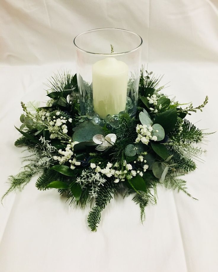 Silver and green table wreath decoration with storm lantern and candle