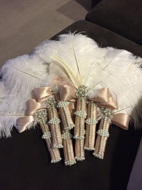 This BEAUTIFUL ostrich feather fan is made of real ostrich feathers, pearls, a rhinestone embellishment, and a color ribbon of your choice. This