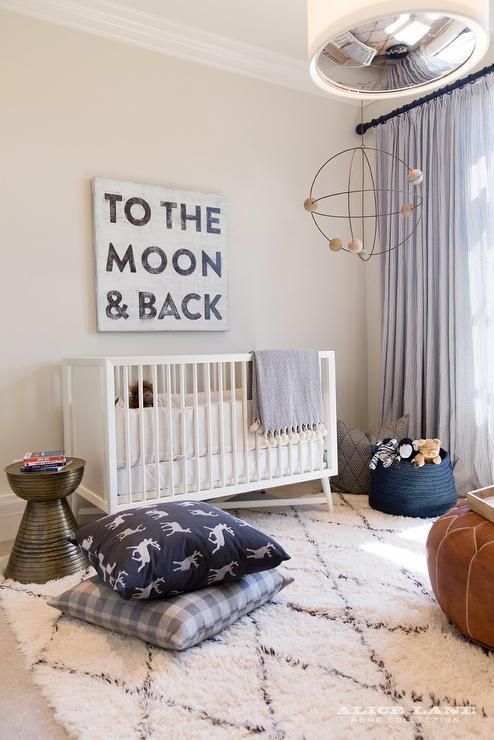 Fabulous white and blue boy's nursery features a To The Moon & Back canvas art over a white DwellStudio Mid Century Modern Crib alongside a metal stool table, navy deer pillow and a gray buffalo check pillow placed atop a beni ourain rug.