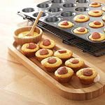 Mini Corn Dog Bites. Mix up an 8.5oz box of corn muffin mix, divide batter into the Mini-Muffin Pan, and add hot dog slices. Bake for 10-12 minutes at 375°.