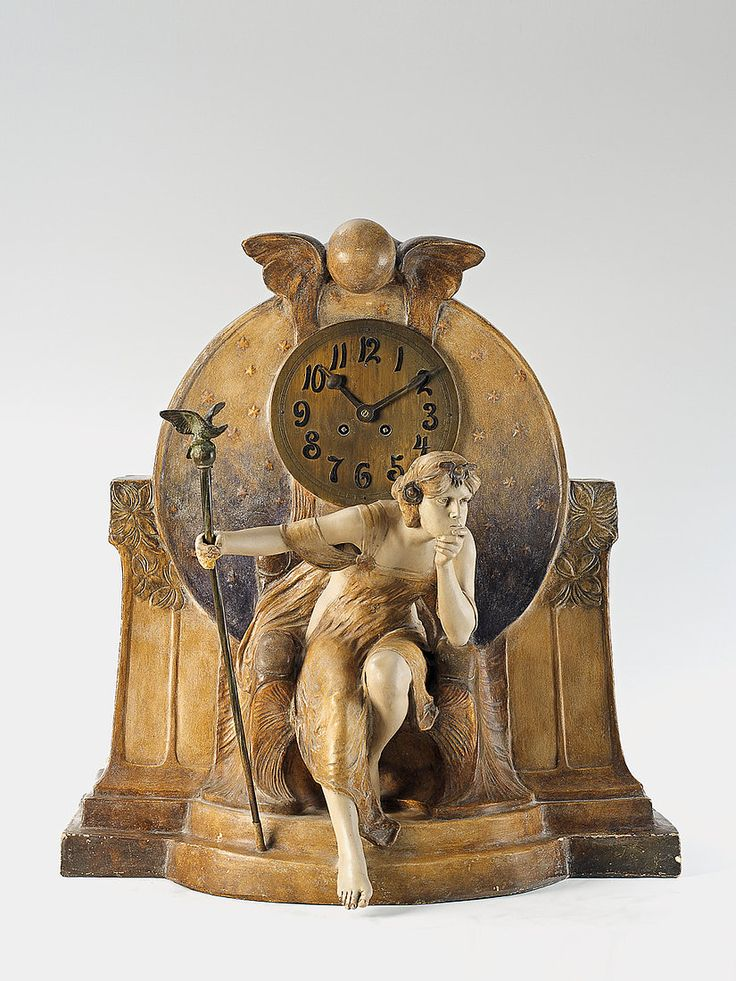 A Vienna gilt ceramic Théodora figure clock. A Goldscheider gilt and painted terracotta and bronze table clock, the movement with half hour strike on spiral gong - Ca. 1903.