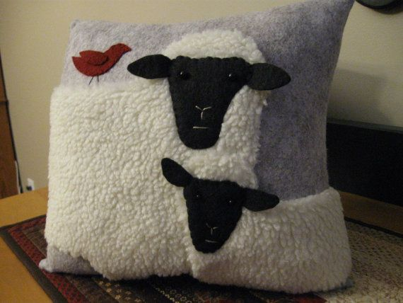 This pillow features two woolly sheep, a Ewe and her lamb and is made using woolly fabric for both sheep. Their faces are done in black wool felt,