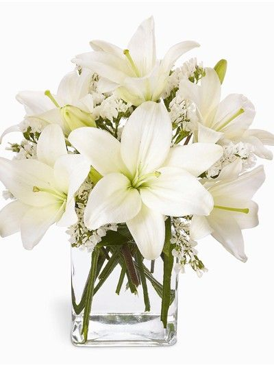 A bouquet of white lilies arranged in a compact square vase