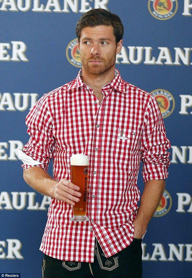 Sheepish: New Bayern Munich signing Xabi Alonso appears slightly awkward during filming fo...