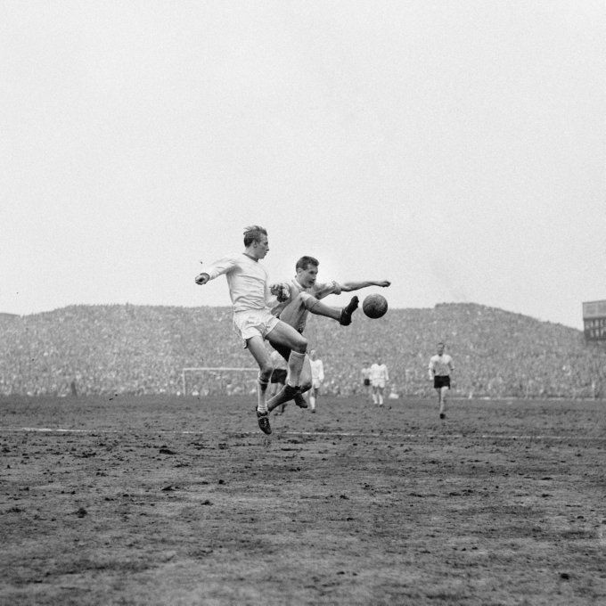 Burly Southampton centre-half Tony Knapp battles Denis Law for the ball as the full expanse of the Holte End roars him on, 1963
