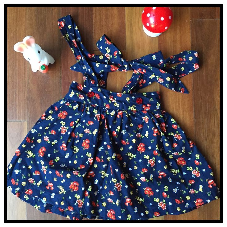 Navy floral girls suspender skirt with red buttons. So cute.