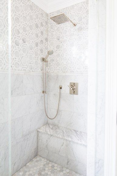 The large scale of the mosaic tile creates the illusion of a space, while a tall wainscot in the shower gives the room balance and proportion. Clayman used a curbless shower for its clean lines and modern aesthetic | archdigest.com