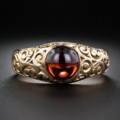 A classic Victorian 'gypsy' style gents, or unisex, ring adorned with deeply engraved scroll work and highlighting a glowing cabochon garnet. 14 karat rosy-yellow gold - circa 1890.