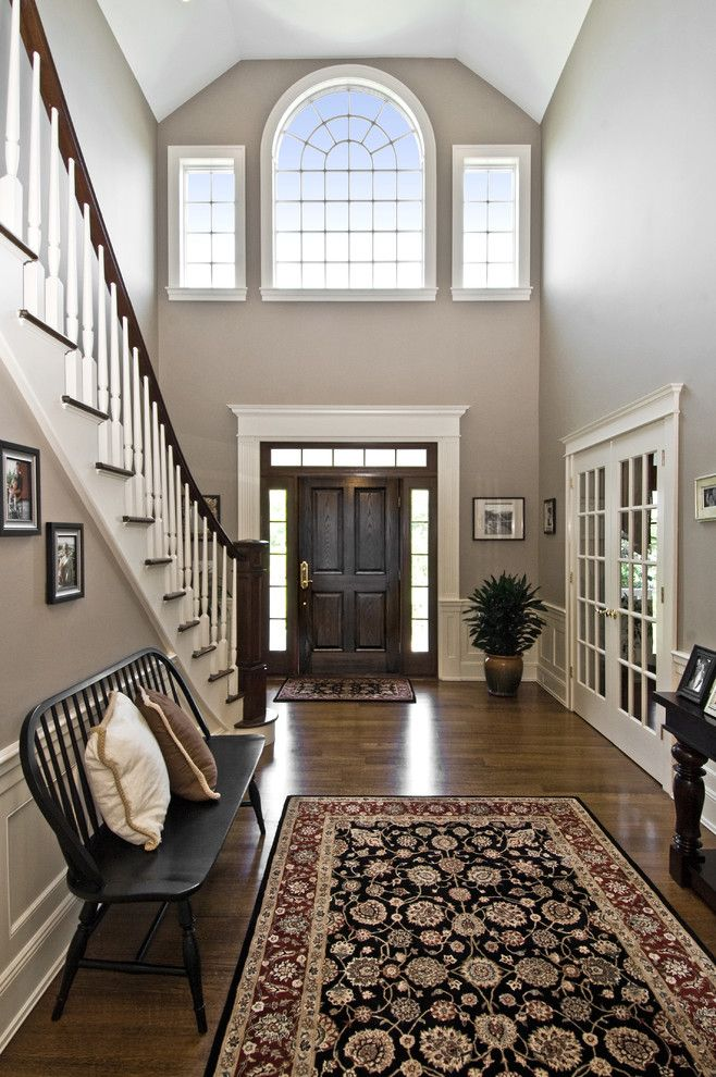 Large two-story foyer, french doors, white and wood staircase, large area rug, black bench | James Traynor Custom Homes