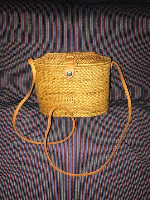 Tall Oval Ata Rattan Shoulder Bag with Leather Snap Closure and Strap with Four Panel Ensign Design. This handbag is not lined.     Ata is in the same family as the Rattan Climbing Palm, although Its a little bit smaller than Regular Rattan.  It is abundant in the Tropical jungles of South East Asia.  Here in Bali, it is used to make fish traps, many household baskets and rice containers.