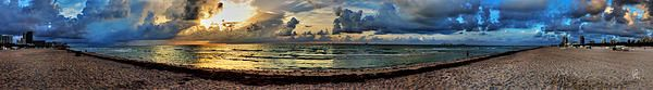 In this sweeping panoramic vista of South Beach in Miami, you can see the sun peek from behind dark storm clouds.