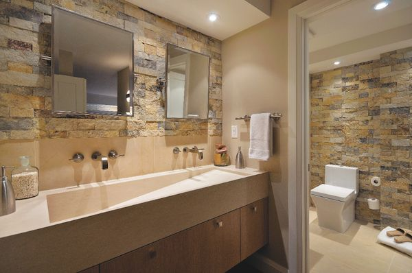 A custom trough sink, wall-mounted faucets, and stone walls.