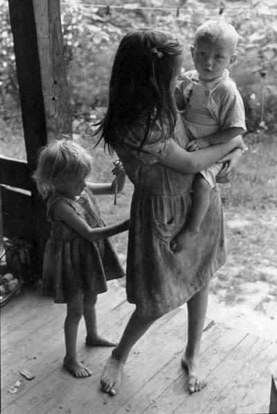 U.S. Girl Holding Little Boy; Smaller Girl Tying Bigger Girl's Dress, Kentucky 1964 // William Gale Gedney