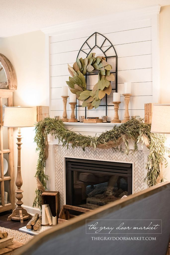 Living Room decor - rustic farmhouse style. Fireplace mantel featuring magnolia wreath over window frame, natural wood turned candlesticks, pretty green garland draped in front of herringbone patterned marble tile faced fireplace. Joanna Gaines, Fixer Upper style.