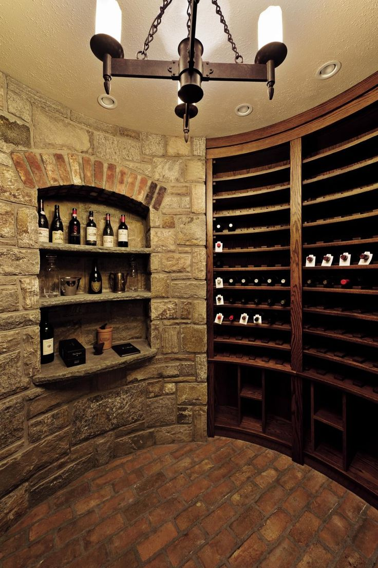 "The circular wine room below the rear turret of this Tudor-style home is filled with custom built-in wine racks and stone shelves. Natural stone is used on most of the walls in the space, and reclaimed brick covers all of the floors.  The entire space is ""reclaimed"" since it replaces what was once a garage and basement. Very little heat (or cooling) is used to make these subterranean spaces function properly."