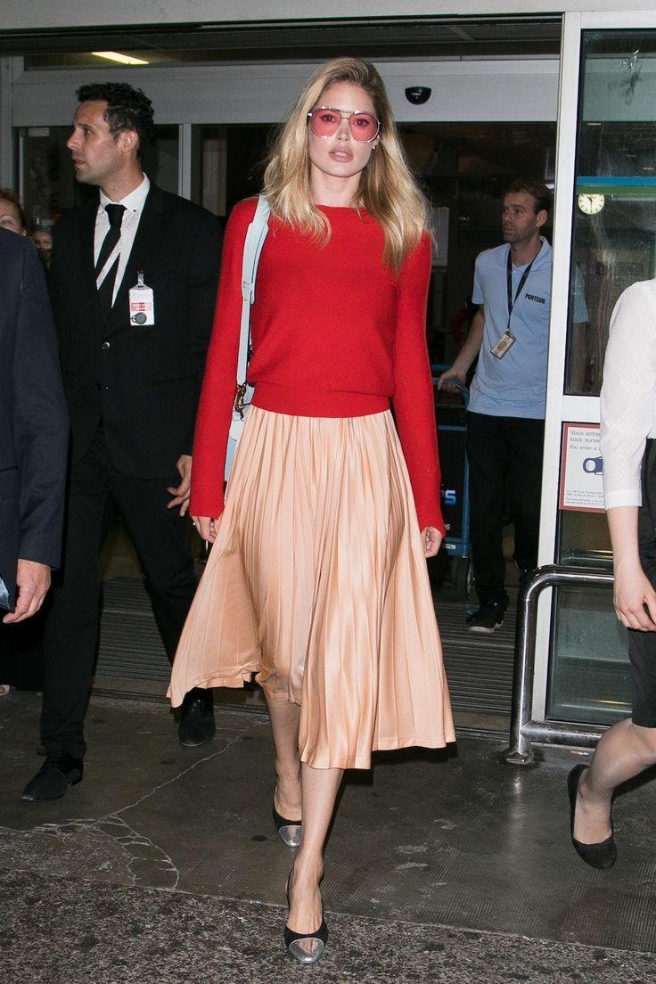 Doutzen arriveert 's ochtends op het vliegveld van Nice in een zalmroze plissé rok en rode trui van Celine - Doutzen Kroes toont de ultieme zomergarderobe in Cannes