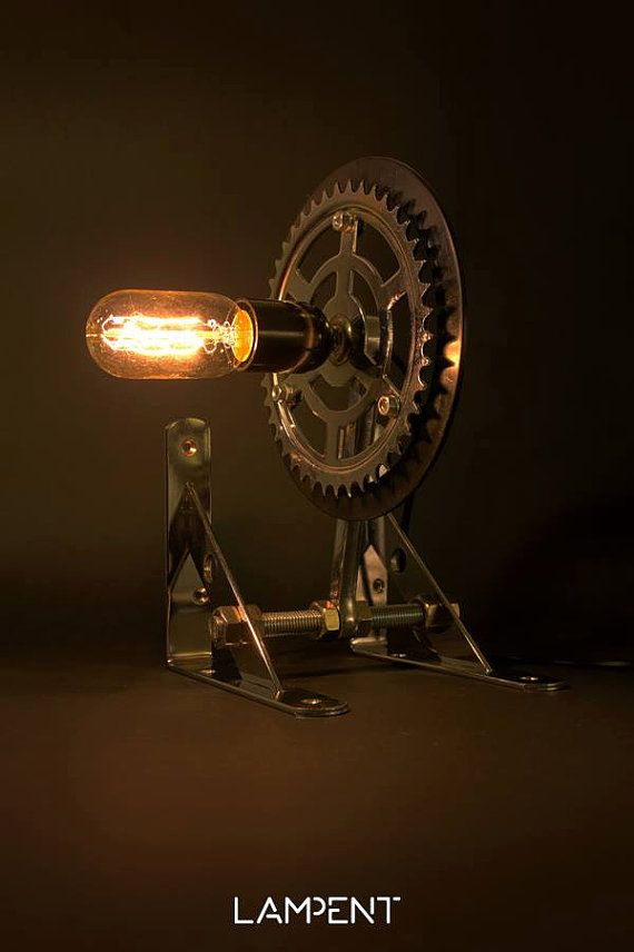 This table lamp is made from a bicycle gear which connects to two wall angles used for shelves. A decorative light bulb is used. The lamp is unique and can create a quite atmospheric ambience in space.