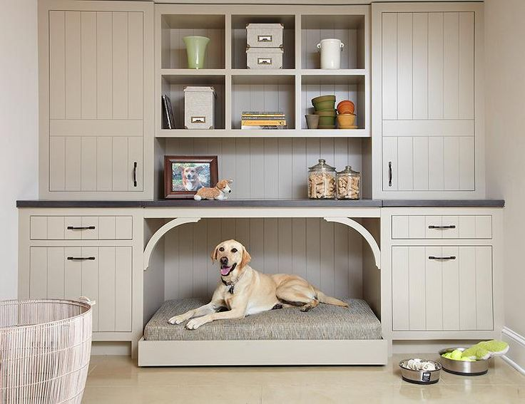 source: Casa Verde Design Cottage mudroom features a built-in dog bed tucked below taupe shelves flanked by taupe cabinets.