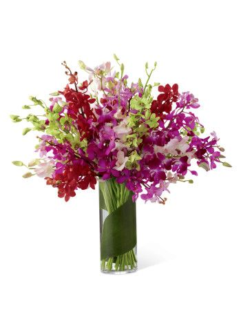 Let your sweet sentiments shine with vibrant color and exuberant elegance. An assortment of brilliant dendrobium orchids in the shades of red, lavender, green, fuchsia, hot pink and pale pink are brought together to create a simply fantastic display. Wrapped in a single tropical leaf and perfectly arranged in a superior clear glass vase, this bouquet will delight your special recipient with its exquisite beauty and long-lasting blooms.