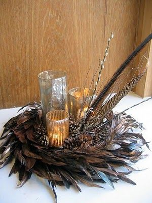 pheasant feathers in a wreath-like shape with small pine cones and candles as centerpiece for Christmas  ---