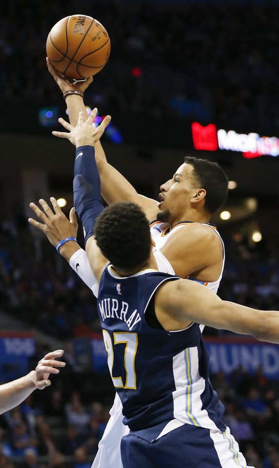 Oklahoma City\'s Andre Roberson (21) takes the ball to the hoop as Denver\'s Jamal Murray (27) defends during an NBA basketball game between the Oklahoma City Thunder and the Denver Nuggets at Chesapeake Energy Arena in Oklahoma City, Monday, Dec. 18, 2017. Photo by Nate Billings, The Oklahoman