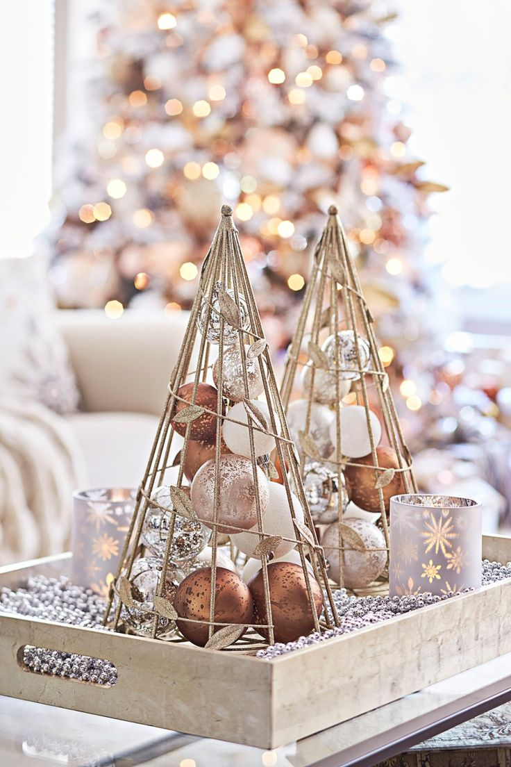 Top your table with a tree tray. Create a Christmas conversation piece for your coffee table by lining a wooden tray with a bed of silvery bead garland and using it to display tree-shape wire cones filled with white and metallic ornaments.