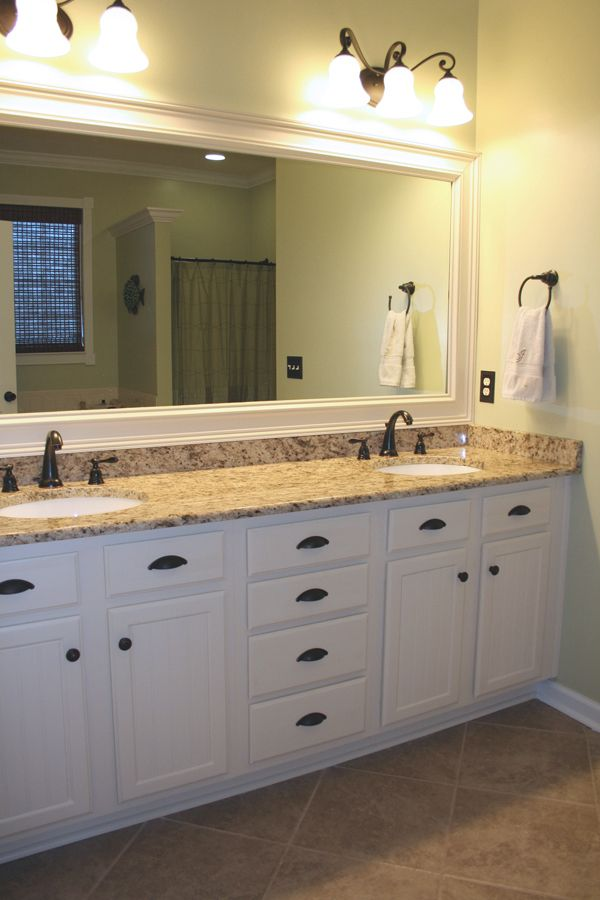 Bathroom - After!  My favorite part. I repainted our oak cabinets with cream colored paint, added oil-rubbed bronze hardware, added a granite countertop, new faucets and lighting, and framed our contractor-grade mirror. We also added beadboard to the faces of our cabinets.