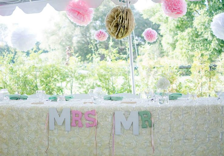 Ivory rosette tablecloth. Pom poms. Backyard wedding. Tent reception. Photo by Eleventh Hour Photography