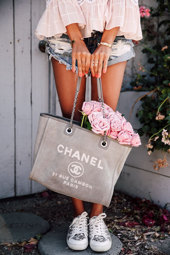 sneakers, ripped jean shorts, ruffled pale pink peasant blouse, Chanel handbag, gold accessories