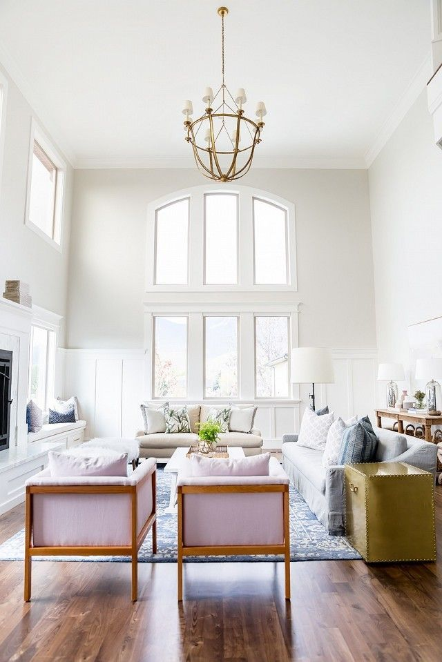 Living room with high ceilings, arched windows, wood floors, matching pastel armchairs, and a chandelier