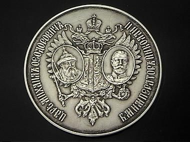 """Obverse side of the Tercenteniary Silver school prize medal 1913, with the portraits of Tsars Michael and Nicholas II, and the coat of arms of the House of Romanov laid on double headed Imperial eagle, for those who graduated with honors in the year of the 300th anniversary of the Romanov dynasty. Diameter 1 11/16 in (42 mm).  Scarce one year type medal.  Reverse with the dates 1613-1913 and a scroll with Cyrillic inscription """"successful""""."""