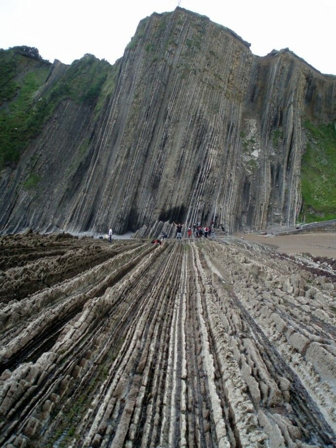 "Flysch Rock Formation in Zumaia, along the Basque coast, northern Spain. Two beaches that contain a geologic treasure of millions of years of the Earth's history.  Hotspots for geologists because it has the llongest continuous rock strata in the world called a 'flysch.""  found to have formed over a period of over 100 million years by the crashing of the waves against the cliffs."