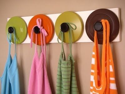 A great way to reuse and recycle using pot lids as hooks! See your local Goodwill for all your home decor and diy projects! www.goodwillvalleys.com/shop
