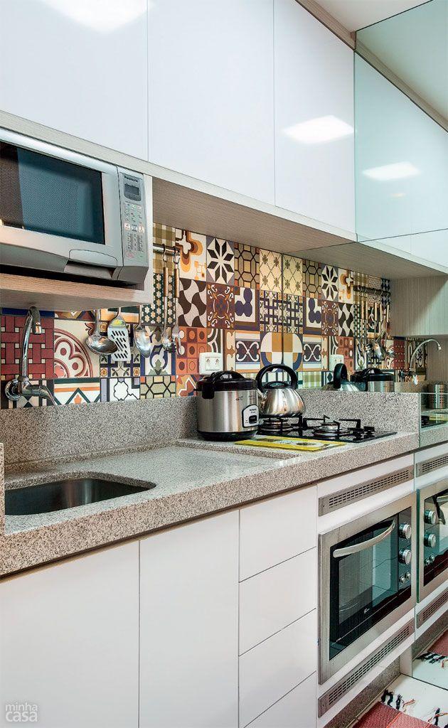 Na cozinha, combinação de revestimento decorado e espelhos – estes aparecem na divisa com a lavanderia, enquanto o patchwork de azulejos  cobre o trecho entre a bancada da pia e os armários planejados.