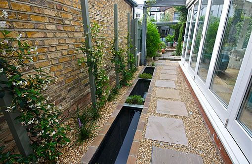 Water feature enhancing a long, narrow side return. Eye-catching rill, a canal of reflective water, complements the modern, glass extension to this Chiswick house. Small planting areas separate the water chambers which, at only 40cm deep, are easy to maintain. Behind the rill, tensioned wires run between timber posts enabling climbing plants to create a living wall, an evergreen backdrop to disguise the boundary wall. Sandstone stepping stones create a path to the rest of the garden.
