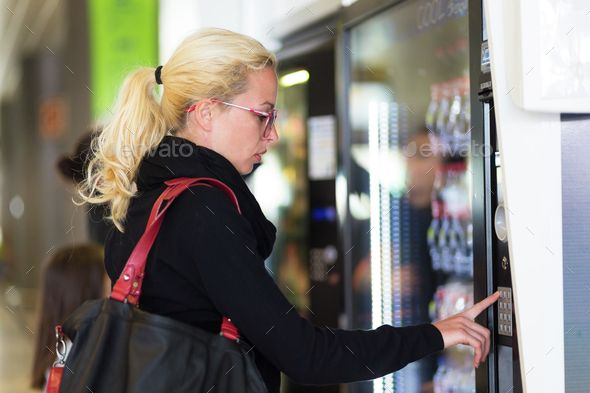 Lady using a modern vending machine by kasto. Casual caucasian woman using a modern beverage vending machine. Her hand is placed on the dial pad and she is looking...
