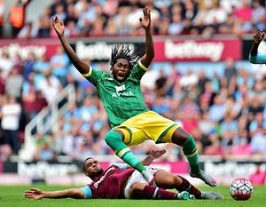 Dieumerci Mbokani of Norwich falls dramatically under Winston Reid's tackle at Upton Park.