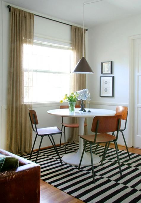 Fix yo windows: curtains should always go to the ceiling or as close to it as possible with the hardware chosen. This window looks great. Love the Saarinen tulip table.