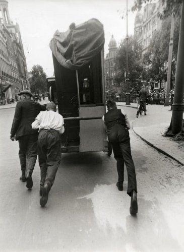 Draaiorgels : Drie mannen duwen een draaiorgel door het centrum van Amsterdam. Nederland, [juli 1937].