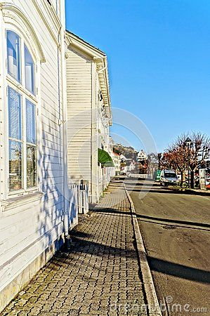 The facades of old wooden buildings, white boards on the walls. Along the asphalt road. HDR. North Sea Coast. Norwegian winter. Risor, Aust-Agder region of Ostlandet. Eastern Norway.