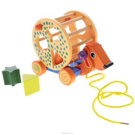 """Oops Деревянная каталка-сортер """"Собака""""  — 1260р. -------------- Деревянная каталка-сортер Oops """"Собака"""" непременно понравится вашему малышу и подойдет для игры как дома, так и на свежем воздухе. Она выполнена из дерева с использованием нетоксичных красок в виде милой собачки. На спине у собаки имеется сортер - вращающийся барабан с отверстиями для трех геометрических фигур, которые при катании звонко гремят. Малышу необходимо подобрать подходящие по формам фигуры и вставить их в…"""