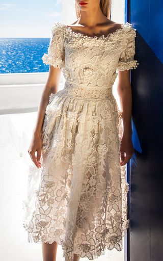 This **Costarellos** Blossom Lace Portrait Neckline Dress features a portrait neckline with embellished trim, short sleeves, allover lace fabrication with embellished detail, and a midi length hemline.