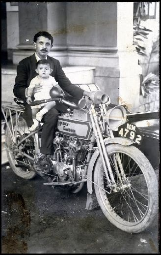 A 1920 Black & white #photograph with the view of Child & Adult on #Harley Davidson #Motorcycle.