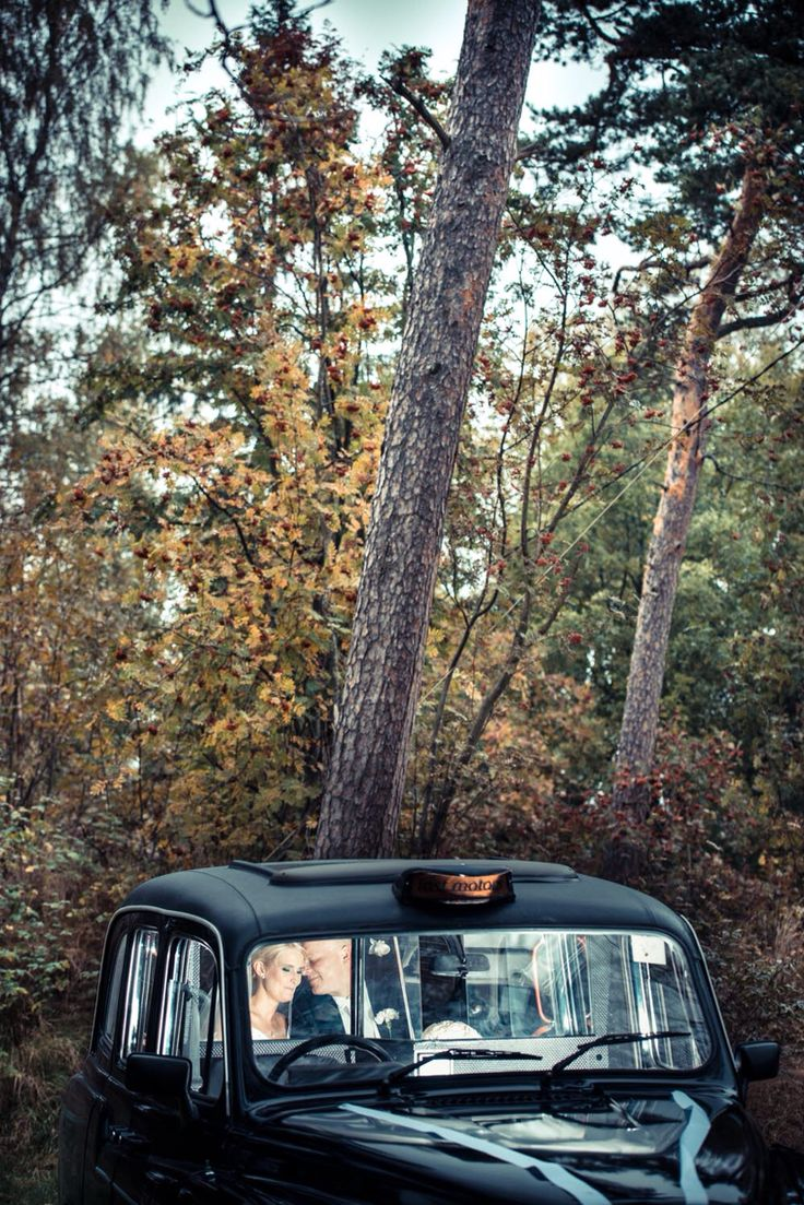 Wedding portrait in parked car by forest.